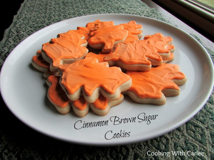 Plate of leaf shaped sugar cookies with cinnamon and brown sugar baked inside decorated with orange royal icing.