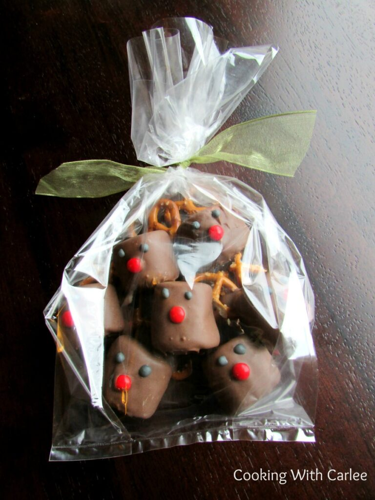 Cellophane bag filled with chocolate dipped marshmallows decorated to look like rudolph the red nosed reindeer tied with a bow ready to be gifted.
