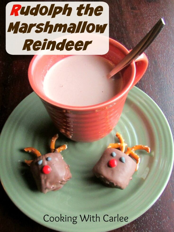 Mug of hot chocolate on plate with two chocolate dipped marshmallows decorated to look like Rudolph the red nosed reindeer.