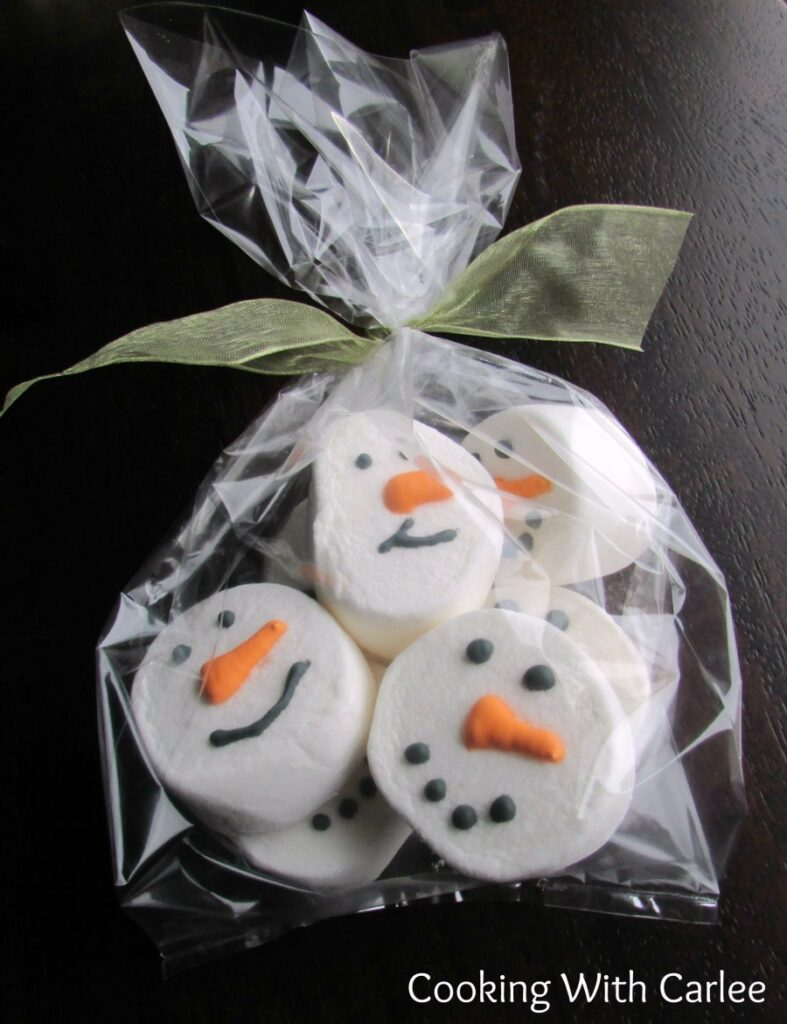 Cellophane bag filled with snowman decorated marshmallows with bow on top.