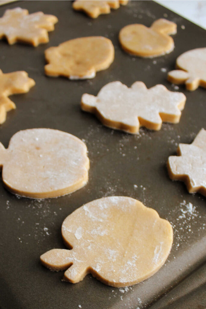 Shapes of cinnamon brown sugar cookie dough on pan ready to bake.