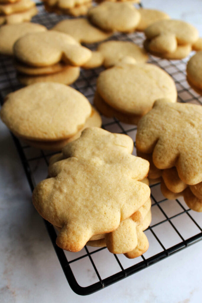 Leaf and apple shaped cinnamon brown sugar cookies stacked on wire cooling rack.
