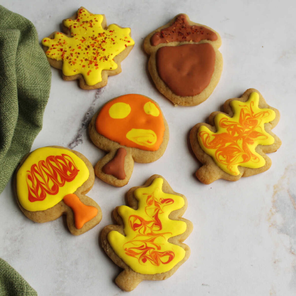 Cinnamon brown sugar cookies cut into leaf, mushroom and acorn shapes and decorated with royal icing.