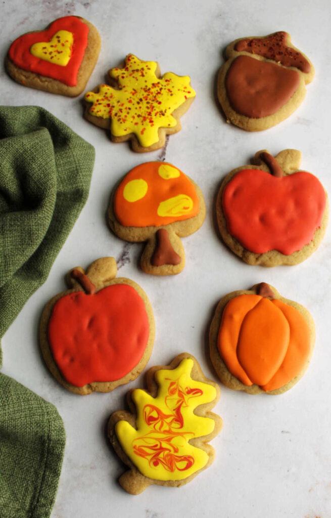 Iced cinnamon brown sugar cookies in shapes of pumpkins, apples, leaves, a mushroom and a heart.