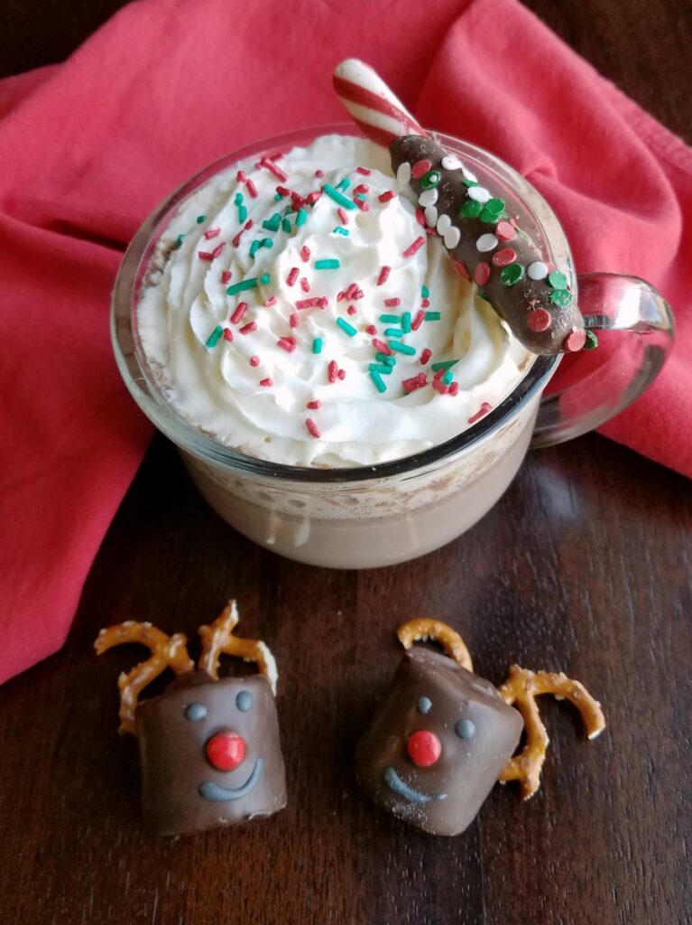Glass mug filled with creamy slow cooker hot cocoa topped with whipped cream and sprinkles garnished with a chocolate dipped peppermint stick with two rudolph marshmallows nearby.