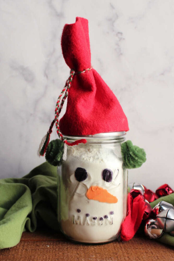 Finished snowman jar filled with white hot chocolate mix powder.