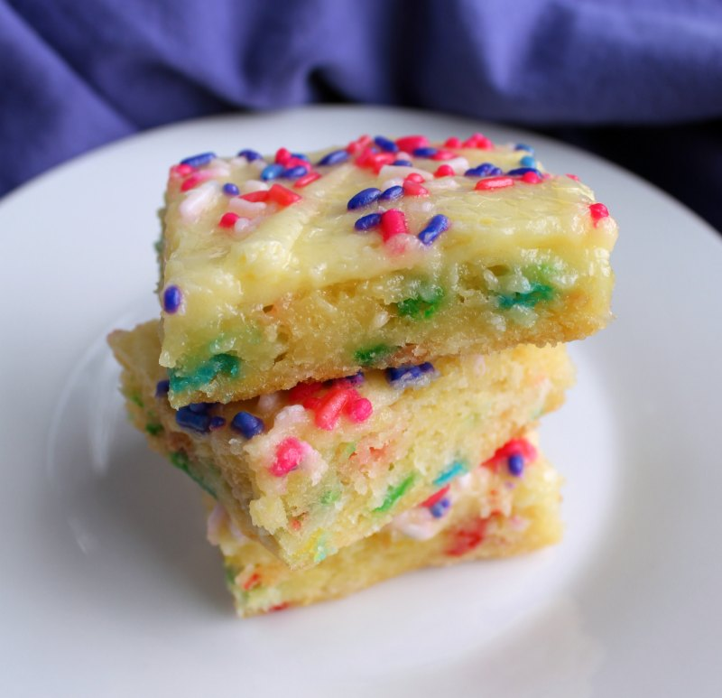 stack of sprinkle filled gooey butter cake slices on plate.