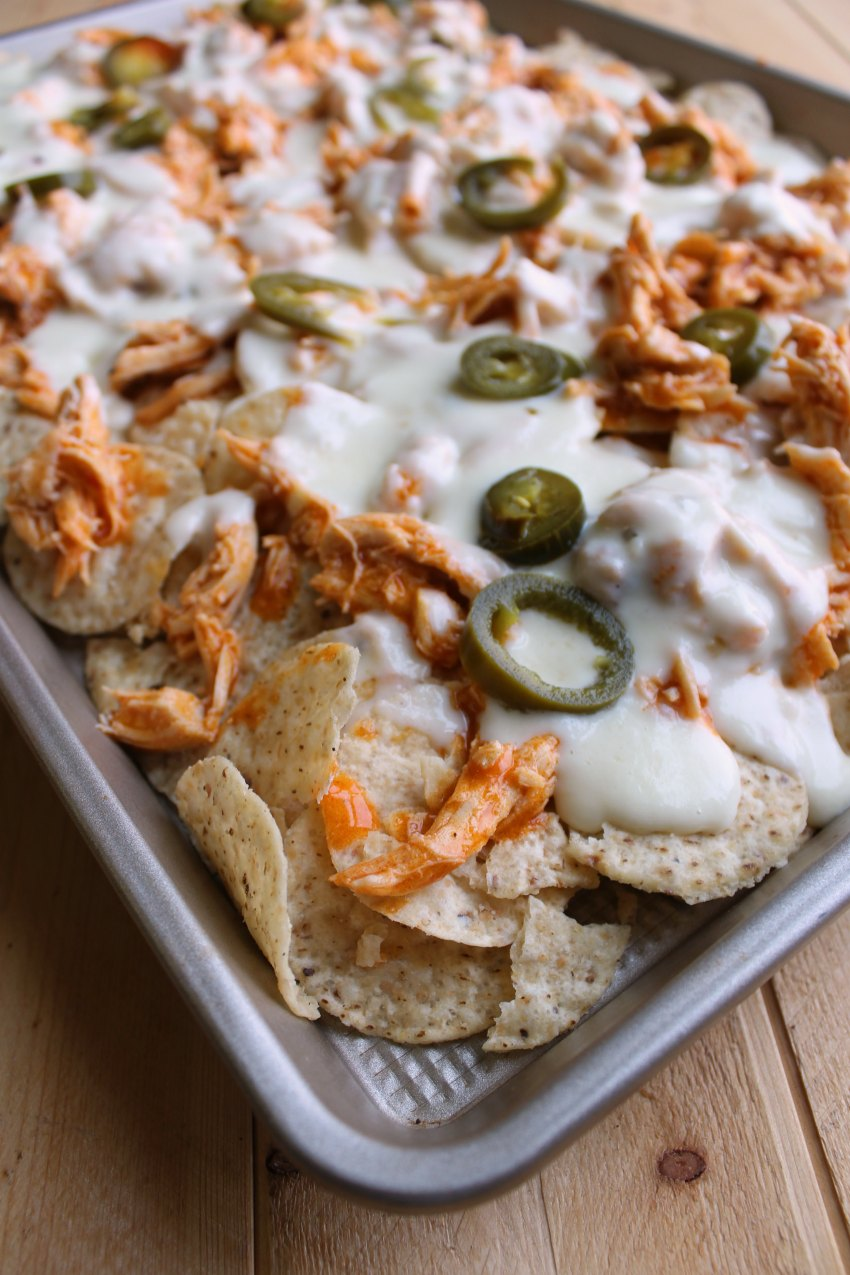 sheet pan full of buffalo chicken nachos with white cheese sauce and jalapenos