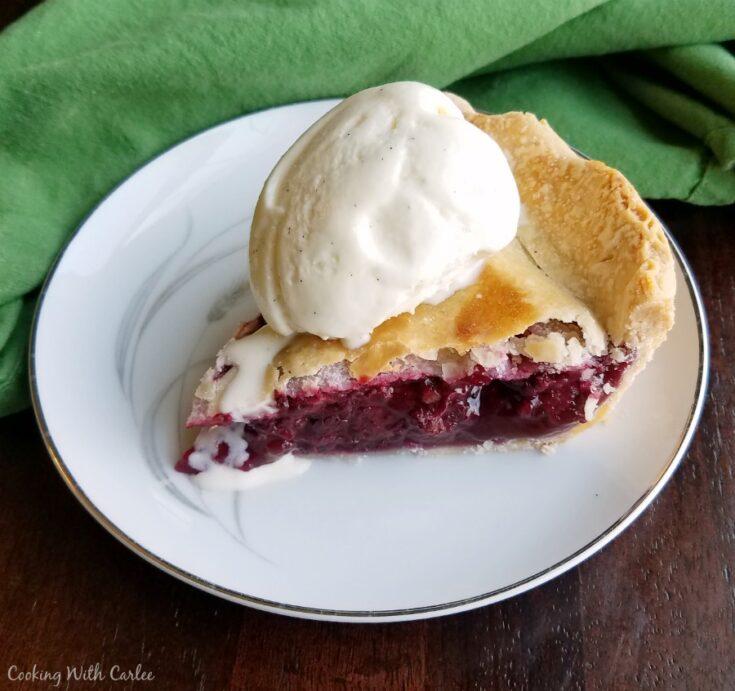 slice of blackberry pie with scoop of vanilla ice cream on top.