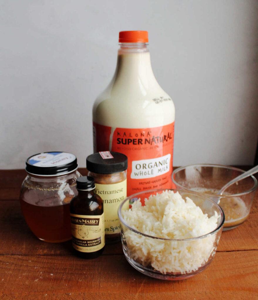 Banana rice pudding ingredients, cooked rice, milk, cinnamon, vanilla, mashed banana and honey ready to be cooked.