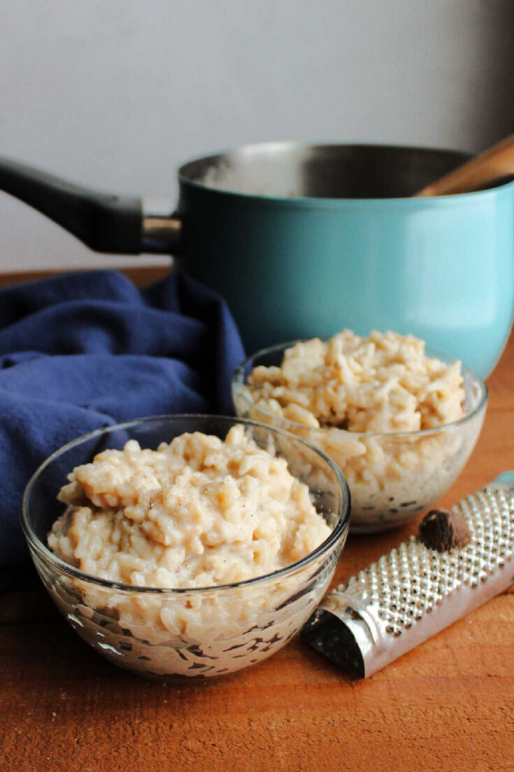 small bowls of banana honey rice pudding with nutmeg grater in front of teal saucepan.