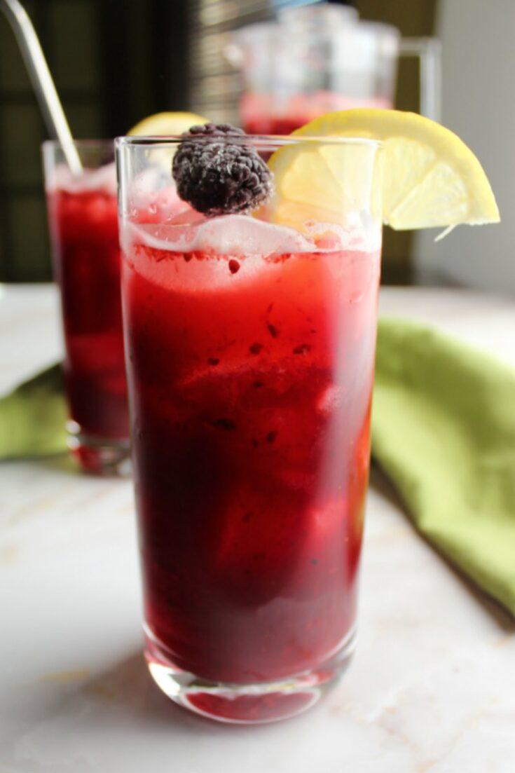 glass of deep purple blackberry lemonade with slice of lemon on the rim, ready to drink.