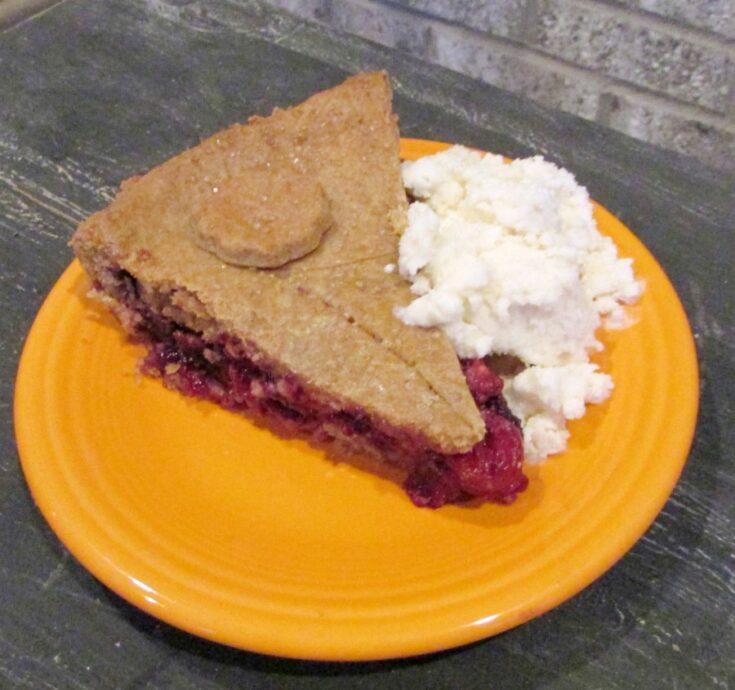 Slice of cherry berry pie with scoop of vanilla ice cream.