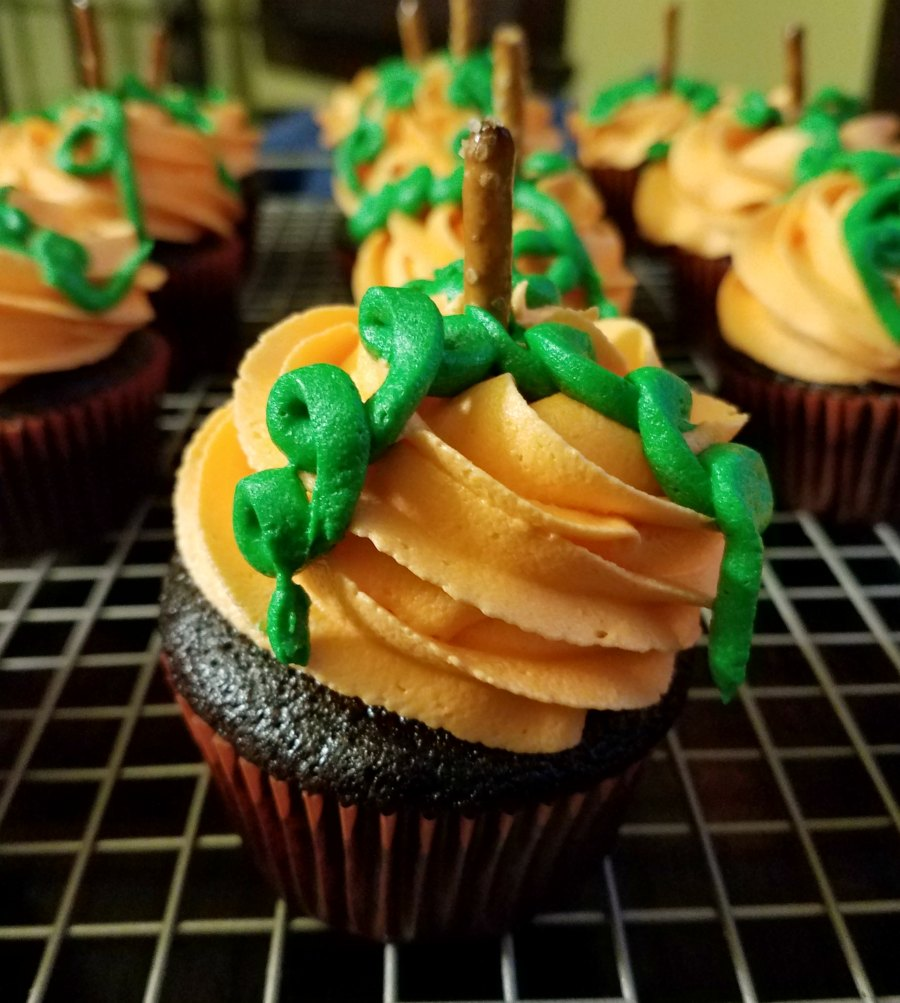 Chocolate cupcakes topped with orange buttercream piped on top decorated like pumpkins.