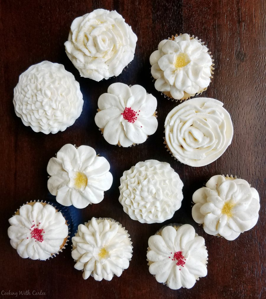 cupcakes decorated with bright white Italian meringue buttercream in various flower shapes