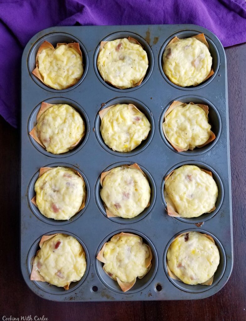 muffin tin filled with freshly baked mini ham and cheese quiche with golden crusts and melted cheesy tops.