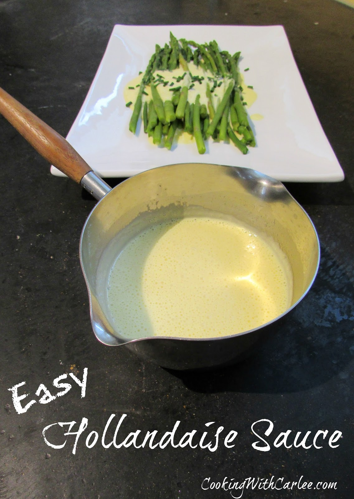 Saucepan with hollandaise sauce in it with platter of hollandaise topped asparagus in background.