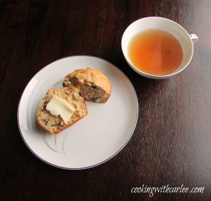Oatmeal raisin sourdough muffin with butter on plate next to tea.