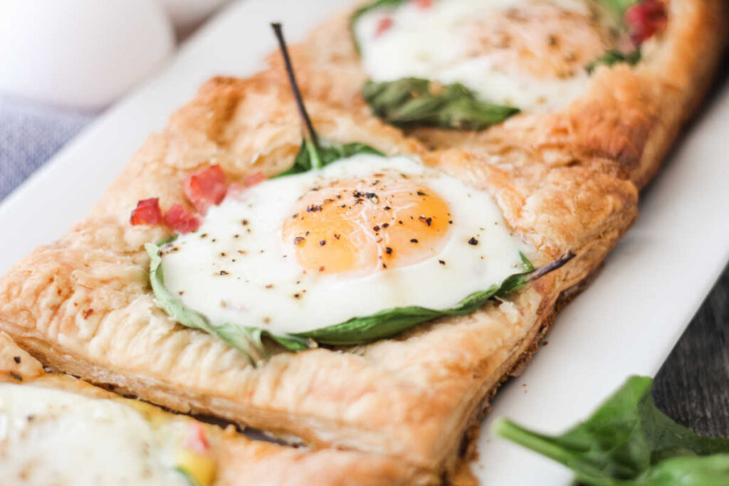 platter of puff pastry topped with eggs, ham and spinach.