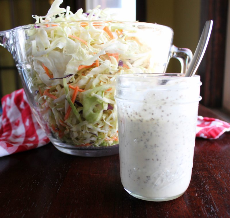 big bowl of shredded cabbage and carrots with a jar of homemade creamy cole slaw dressing.