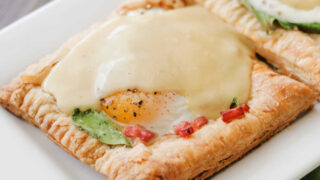 Puff pastry eggs benedict tart with spinach, ham and hollandaise sauce ready to eat.