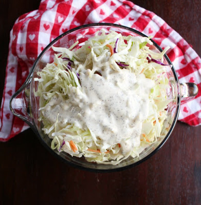 bowl of shredded cabbage and carrots with dressing poured over the top