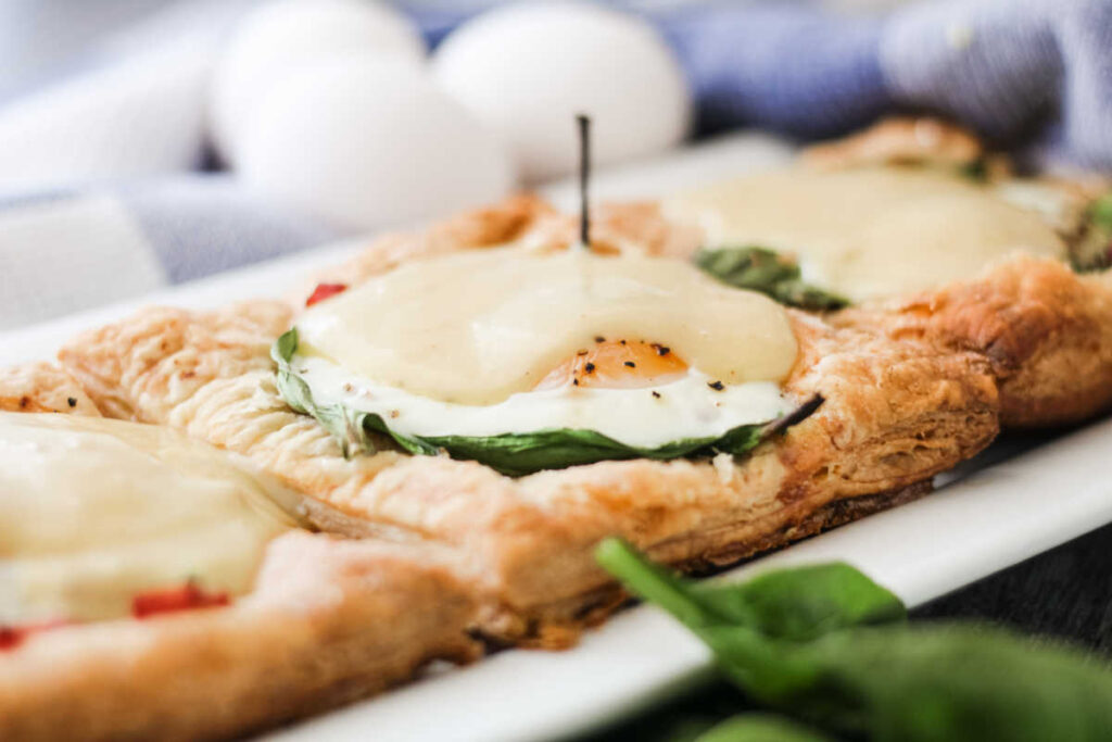 Looking across puff pastry tart topped with egg, spinach, ham and hollandaise sauce ready to eat.