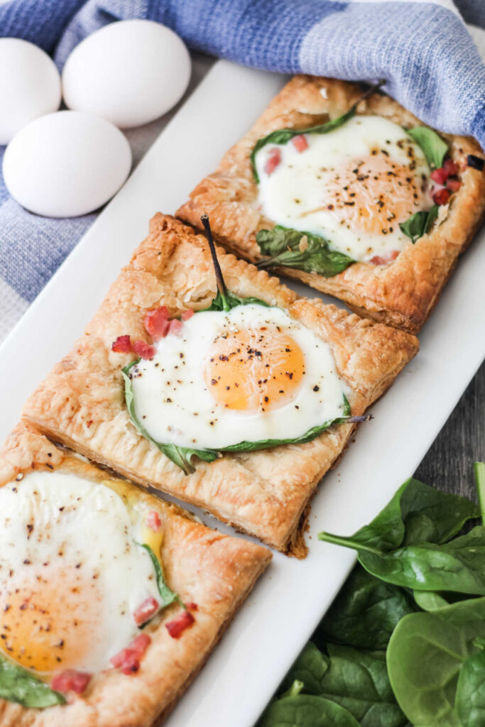 Platter of golden puff pastry squares topped with ham, spinach and eggs baked to perfection.