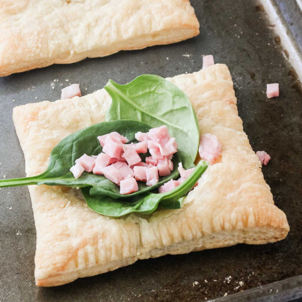 Spinach and ham on top of square of puff pastry.