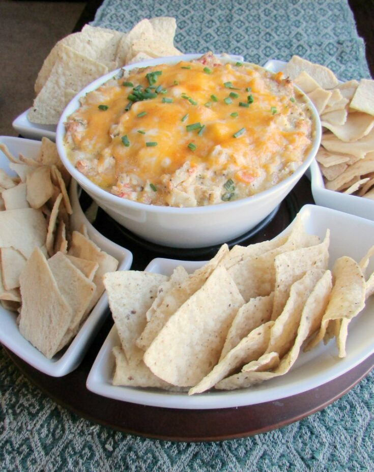 Chip and dip server with tortilla and pita chips with big bowl of hot gooey cheesy shrimp dip in center.