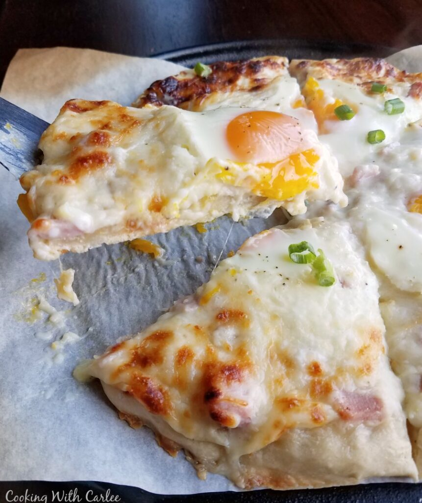 lifting slice of creamy white pizza with gooey egg on top