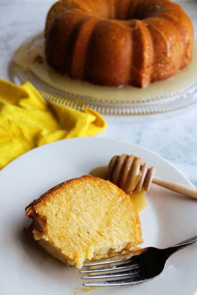 Fork next to slice of honey lemon bundt cake with bite missing.