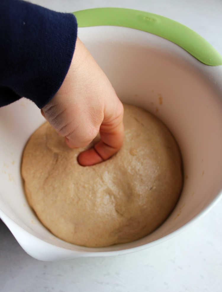 bowl of proofed sourdough sandwich bread dough with finger imprint