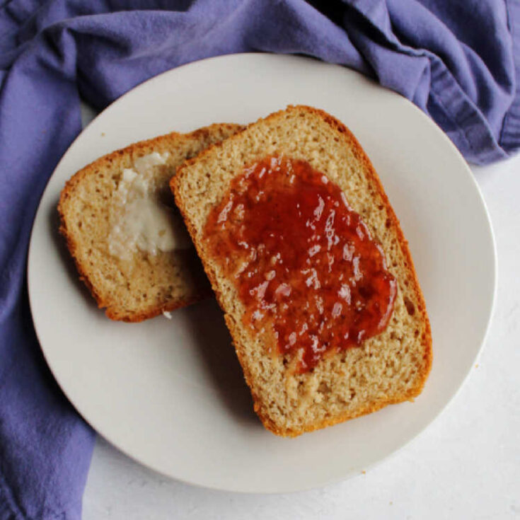 plate with two slices of toasted sourdough wheat bread, one spread with butter the other with honey