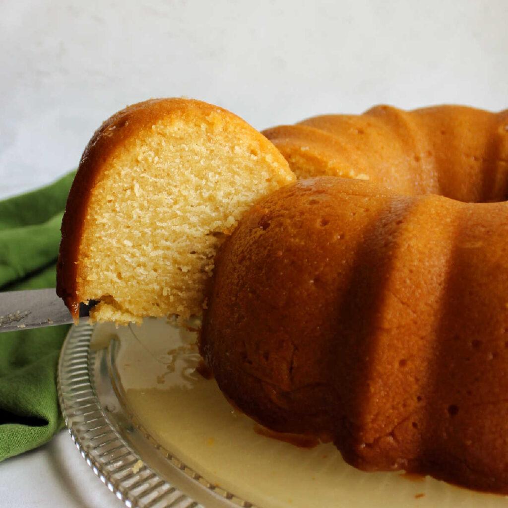 Lifting a slice of honey lemon bundt cake.