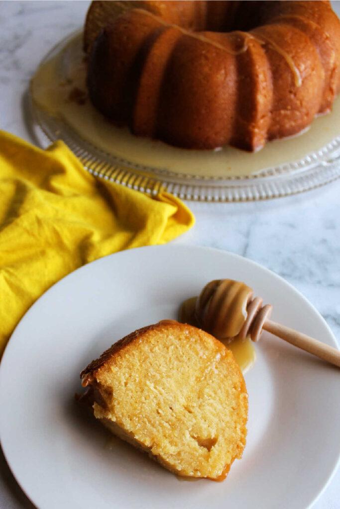 Slice of honey lemon bundt cake on plate with wood honey drizzler nearby.