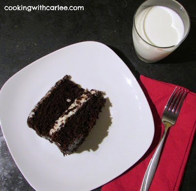 Slice of ding dong cake on plate with glass of milk and fork nearby.