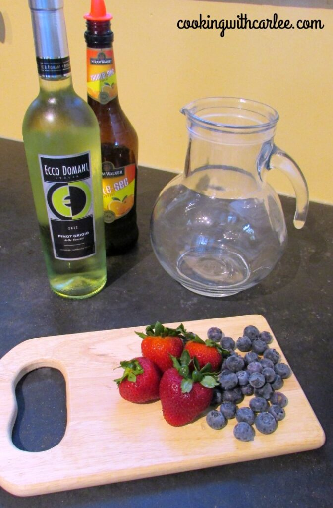 Bottle of wine, triple sec, berries and pitcher ready to be made into sangria.