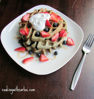 stack of blueberry sourdough waffles on a breakfast plate topped with berries, whipped cream and drizzled with maple syrup