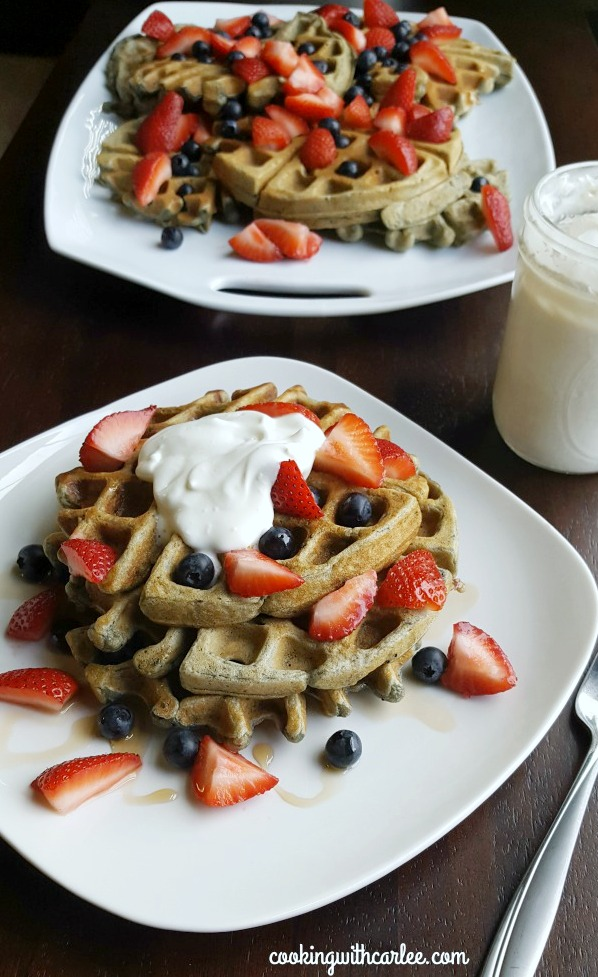 plate of blueberry sourdough waffles with strawberries and maple whipped cream with jar of whipped cream and platter of waffles in background