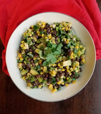 Bowl of corn and black bean salad with avocados, lime and cilantro.