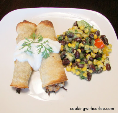 pork taquitos with sour cream served with corn and black bean salad