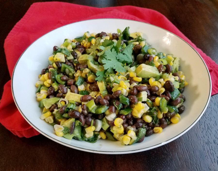 Bowl of avocado, corn and black bean salsa with cilantro.