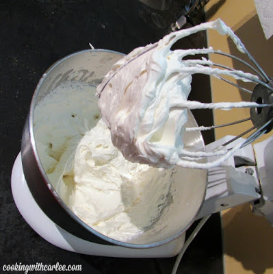 mixer bowl of cream cheese whipped cream on beater