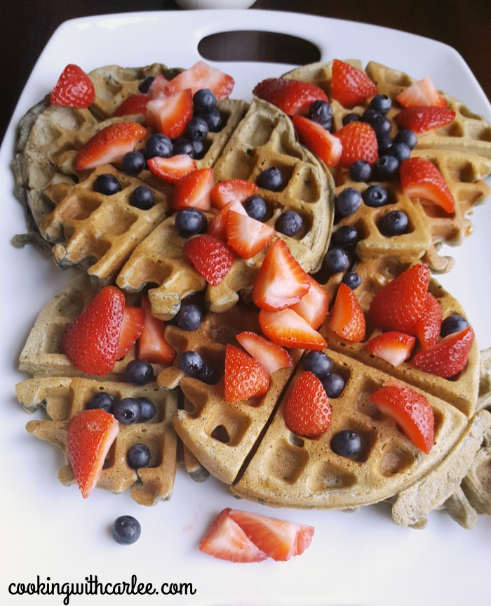 close up of blueberry sourdough waffles with fresh berries on top.