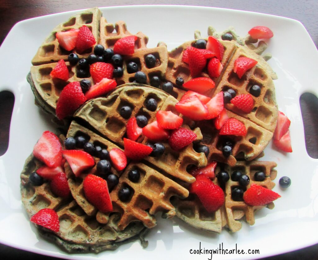 platter of blueberry sourdough waffles sprinkled with more blueberries and pieces of fresh strawberries.