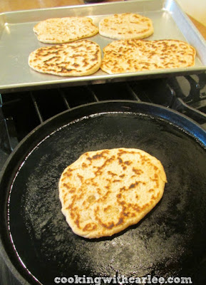 Pita bread cooking on cast iron pan with more pitas in the background.