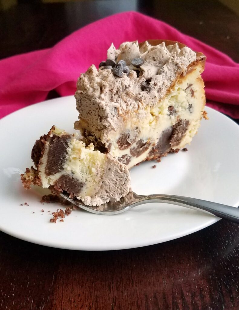 Bite of cheesecake with chunks of brownie baked inside on fork, ready to eat.