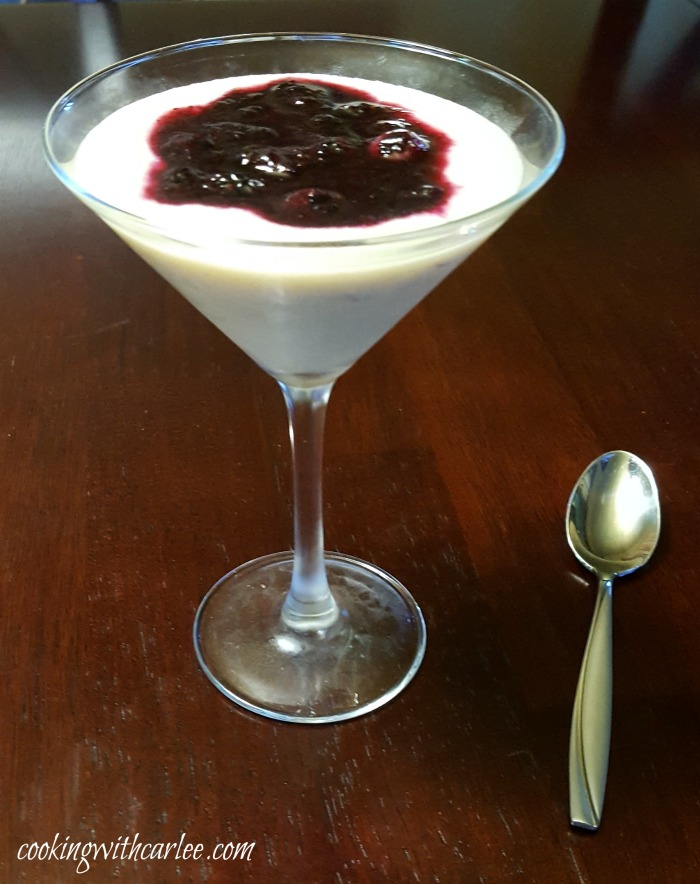 martini glass filled with creamy cornmeal budino and blueberry sauce with a spoon nearby ready to eat.
