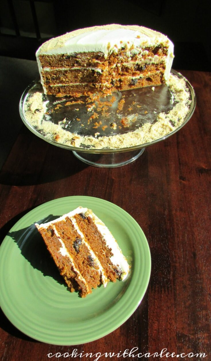 Slice of layered carrot cake with raisins on plate, ready to eat.